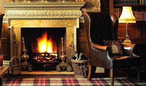 Старинная гостиная с камином и удобным кожаным креслом